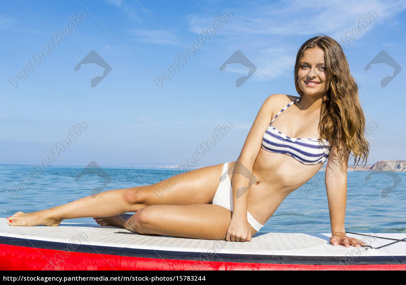 woman, sitting, over, a, paddle, surfboard - 15783244