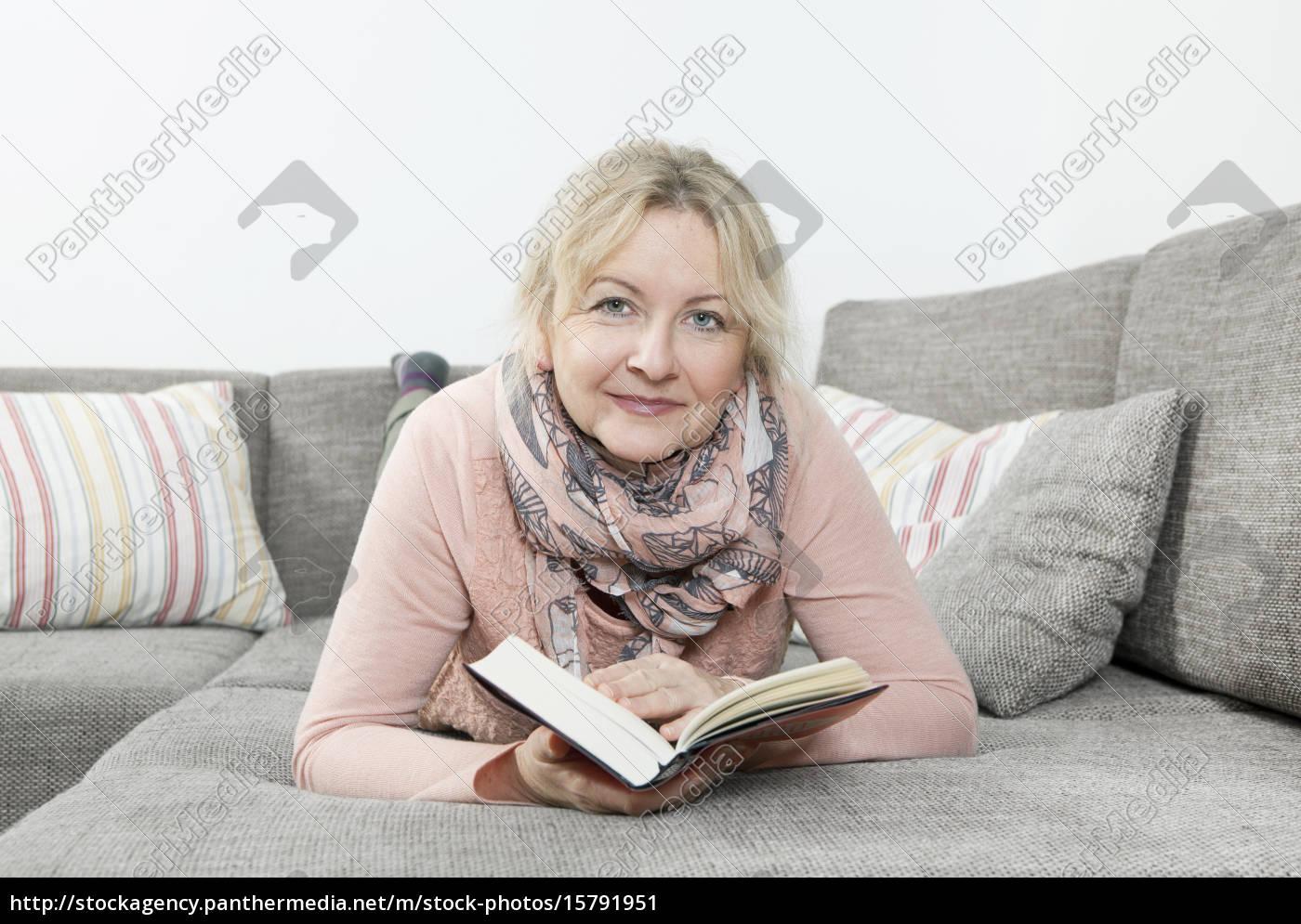 woman, reading, book, on, sofa - 15791951