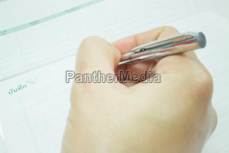 hand on metallic pen write on