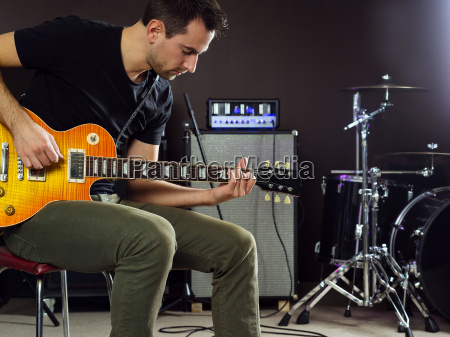 guitarist sitting and playing on stage