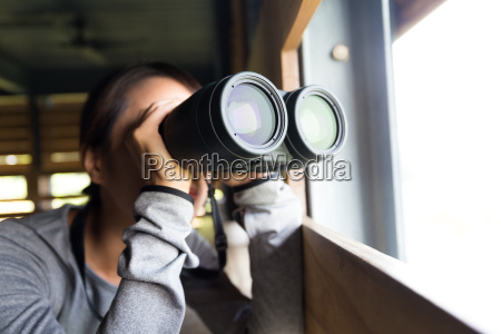 woman looking though the binoculars at