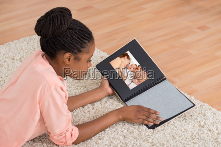woman smiling while looking at photo