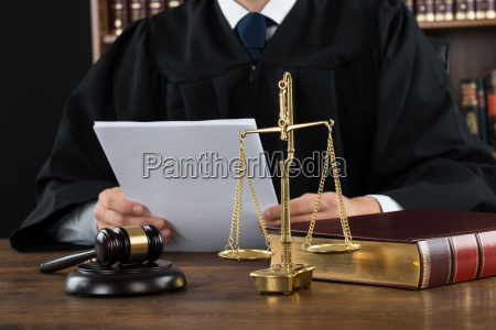 judge reading documents at desk in