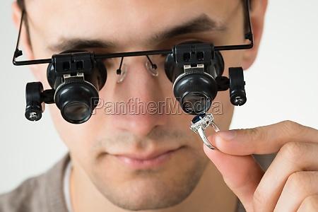jeweler examining diamond ring with magnifying