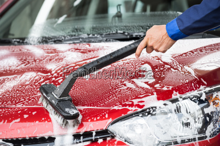 washer cleaning red car at service