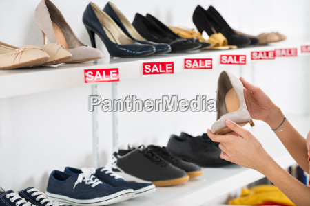 woman buying shoe in retail store