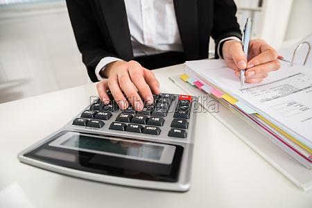 businesswoman doing financial calculation at desk