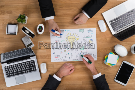businessmen making strategy at wooden desk