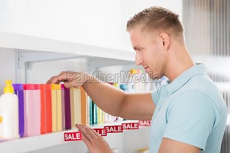 male customer selecting cosmetic bottle