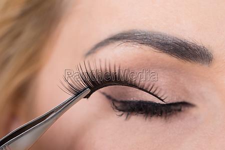 false eyelashes being put on womans