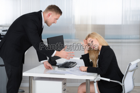 boss shouting at employee sitting at