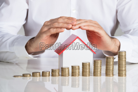 businessman protecting house model with stacked