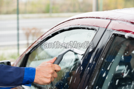 serviceman cleaning car window at service