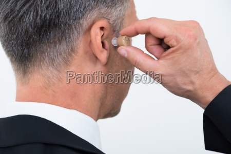 businessman inserting hearing aid in ear