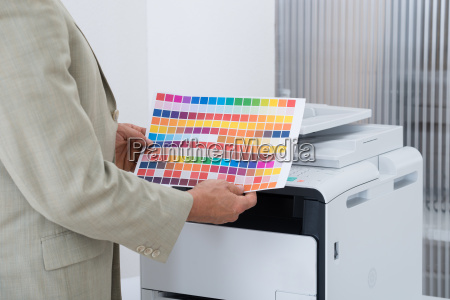 businessman holding multi colored paper by