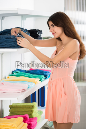 woman choosing jeans in store