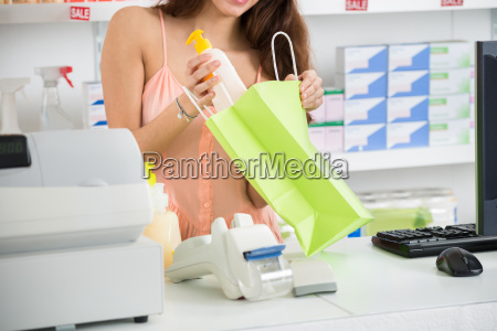 saleswoman putting product into bag at