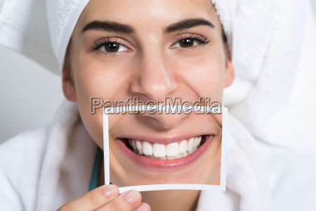 woman holding photo of toothy smile
