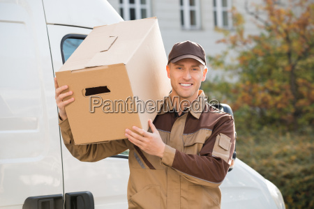 delivery man carrying cardboard box on