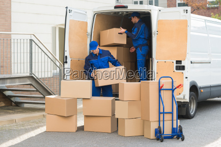 delivery men unloading boxes on street
