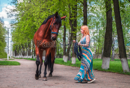 young blonde leads a horse