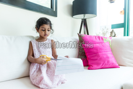 little girl cutting the paper