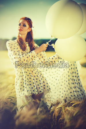 attractive redhead woman with balloons
