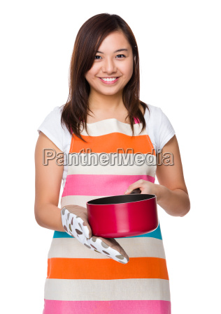 asian young housewife cooking with saucepan