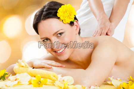 happy woman receiving back massage at