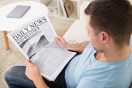 man reading weather news on newspaper