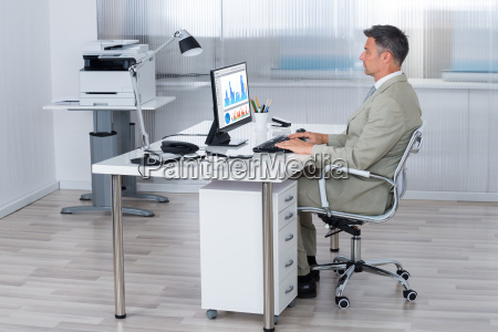 businessman using computer at desk in