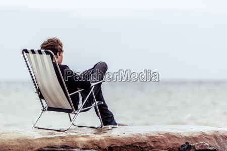 pensive teen on his chair facing