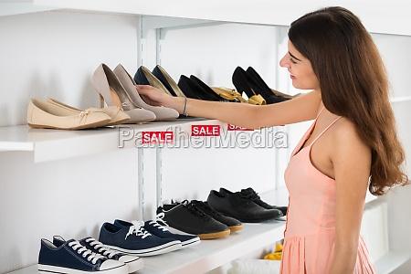 happy woman choosing shoes from shelf