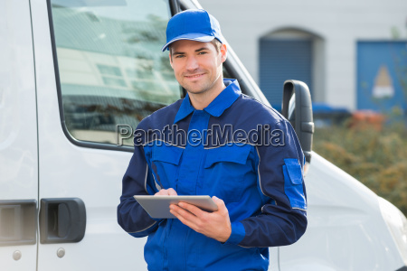 delivery man smiling using digital tablet