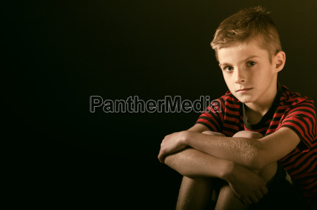 serious boy hugging his knees against