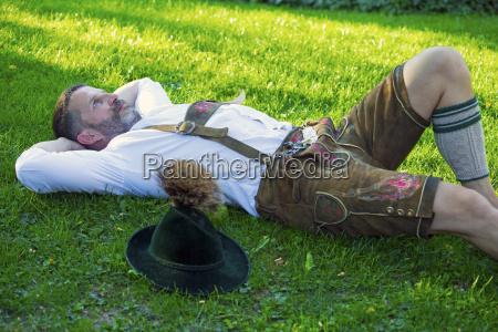 bavarian man lying on the grass