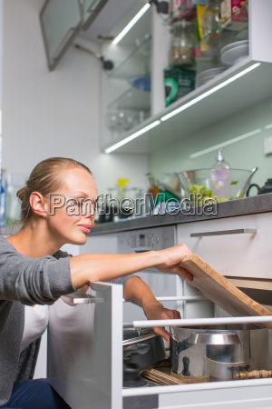 young woman washing dishes in her