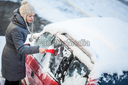 young woman cleaning her car from