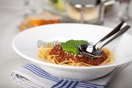 teller mit spaghetti bolognese und basilikum