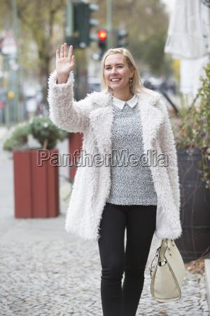 woman walking and waving
