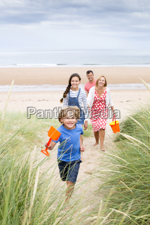 family walking up the sand dunes