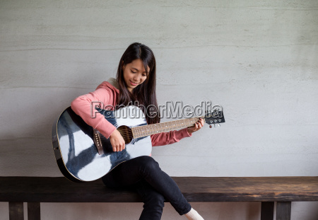 asian woman play with guitar at