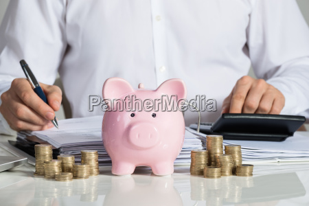 businessman calculating invoice with piggybank and