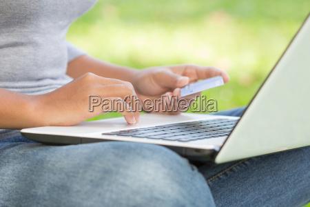 closeup woman using credit card purchase