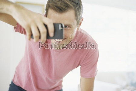 smiling man taking a picture with