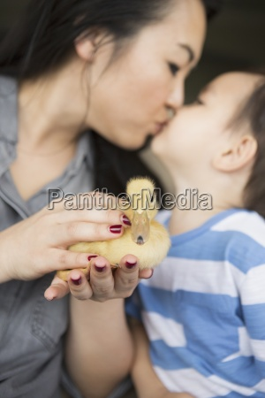 woman holding a yellow duckling in