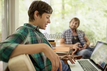 a woman sitting using a laptop