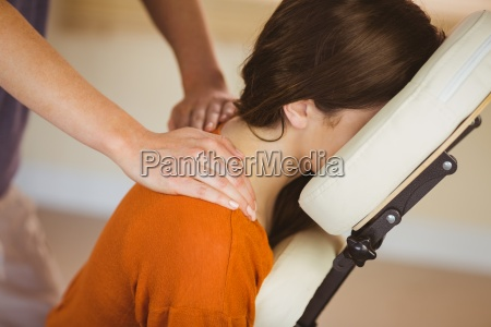 young woman getting massage in chair