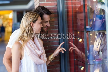 smiling couple going window shopping and