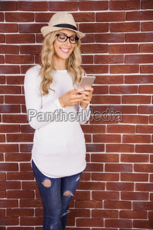 gorgeous smiling blonde hipster using smartphone